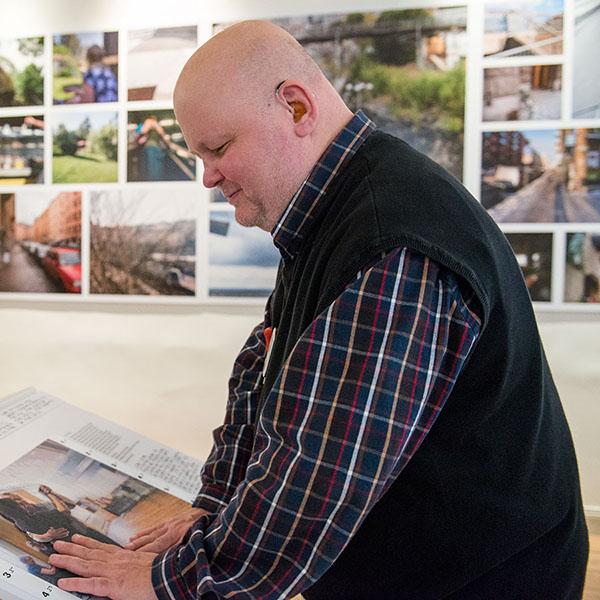 Rolf Eriksson, fotograf med dövblindhet, känner på ett av sina taktila fotografier i utställningen Våga se! på Stadsmuseet i Stockholm 2014. Foto: Truls Nord.